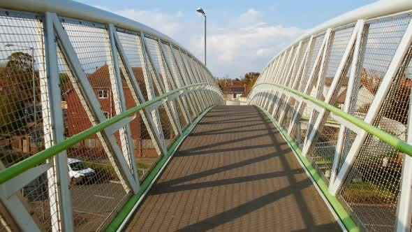 Wlaking Along Suspended Bridge over Motorway