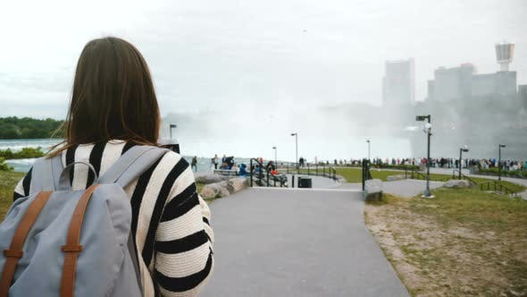 Thumbnail for Camera Follows Thoughtful Local Woman Walking Towards Crowded Observation Deck at Mighty Niagara