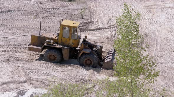 Thumbnail for An Old Bulldozer Moves Sand Using a Bucket on Construction Site