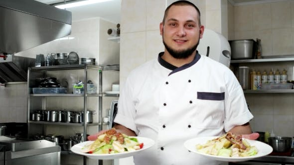 Thumbnail for Portrait Of a Chef, Cook Holds Dishes With Salads, Ready Meals Shows, Looking At The Camera, Smiling