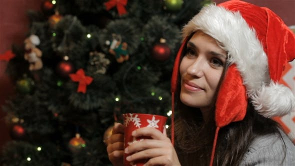 Thumbnail for Woman In Santa's Hat Drinking Some Beverage