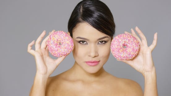 Thumbnail for Happy Vivacious Woman Holding Two Pink Donuts