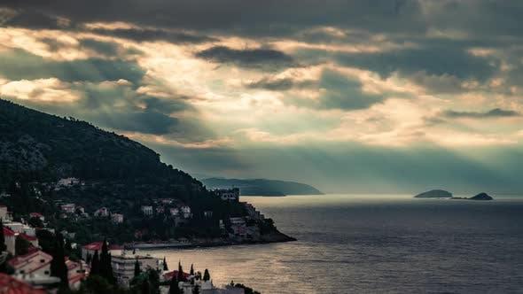 Thumbnail for Zeitraffer von Sonnenstrahlen, die durch Wolken über das Meer strahlen