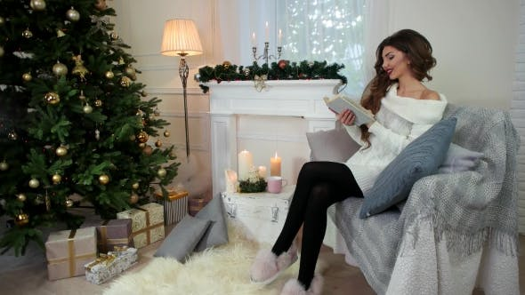Cover Image for Young Woman Relaxing and Reading Book, While Sitting on the Couch, Woman Wearing a Warm Knitted