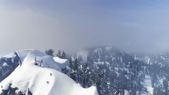 Thumbnail for Blue Hazy Mountain Ridge Snow Aerial In Pacific Northwest Fog