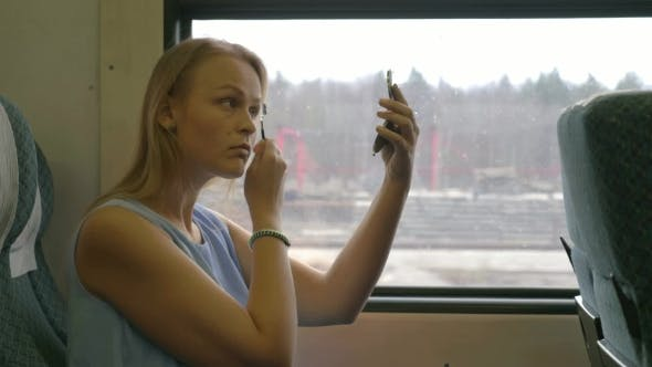 Thumbnail for Young Woman Putting Make-up in Train