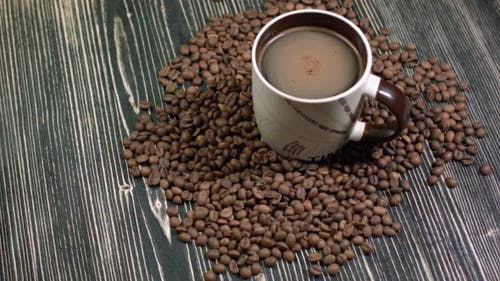 Cup of Coffee and Grains on Table on Dark Background, Fragrant Hot Drink