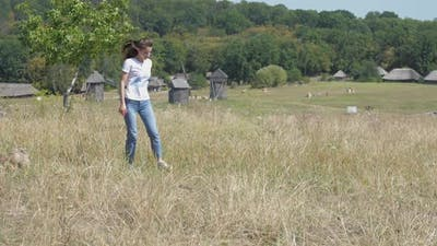 Young Woman with Long Loose Hair Jumps on Yellow Meadow