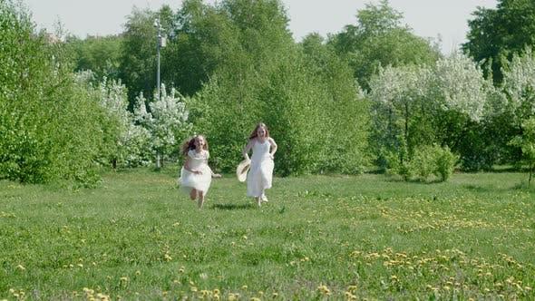 Zwei Mädchen Teenager in weißem Kleid Laufen auf grünem Rasen im blühenden Garten. Laufende Girl Friends auf