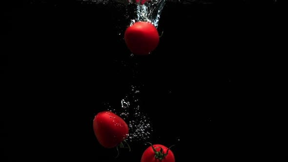 Thumbnail for Fresh Ripe Tomatoes Falling Into Clean Water With Air Bubbles And Droplets On Black Background
