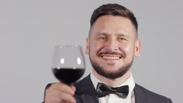 Cover Image for Portrait of Smartly Dressed Man Raising Wine Glass