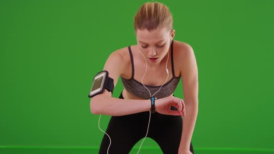 Woman runner using smartwatch fitness tracker while running on green screen
