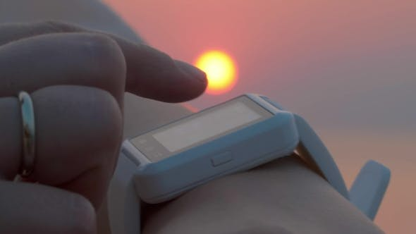 Thumbnail for Using Smart Watch at Sunset