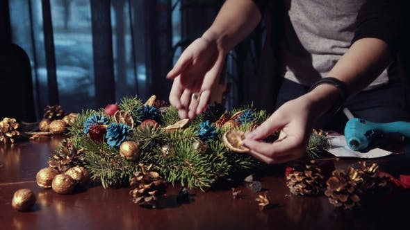 Thumbnail for Crop Hands Decorating Christmas Wreath