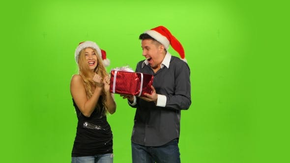 Thumbnail for Young Man Giving a Christmas Present To His Surprised Girlfriend. Green Screen