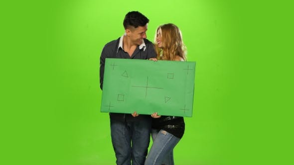 Thumbnail for Energetic and  Beautiful Couple Holding Up a Blank Sign, Green Screen