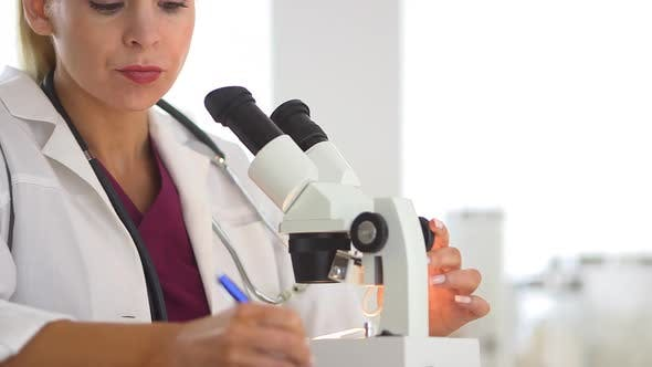 Thumbnail for Medical researcher using microscope and writing notes