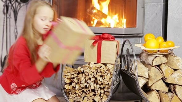 Thumbnail for Adorable Little Girl Opening Christmas Gifts Near Fireplace