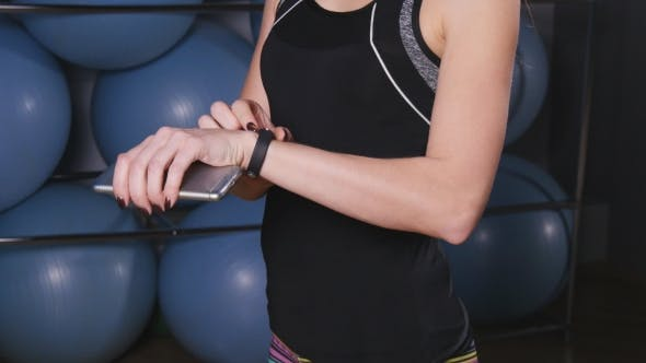 Woman with Heart-rate Watch and Smartphone in Gym