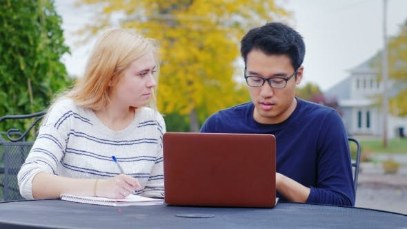 Cover Image for Two Business Man - Asian Man and Caucasian Woman Communicate, Work with a Laptop. The Summer Terrace