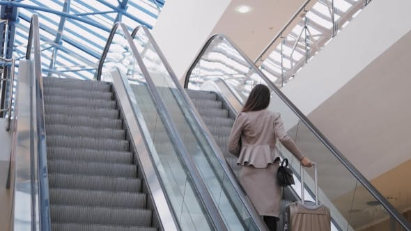 Thumbnail for Full Length of Confident Businesswoman Standing on Escalator with Laggage in Airport. Business Woman