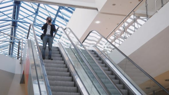 Thumbnail for Confident Businessman Standing on the Escalator, He Is Smiling and Waiting with Camera