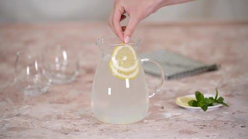 Female Hand Puts a Slice Lemon Ana Mint in Jug for Lemonade