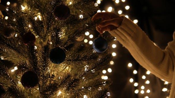 Thumbnail for Hangs Christmas Ball On Tree