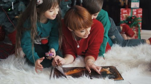 Family Book Reading Near Christmas Tree