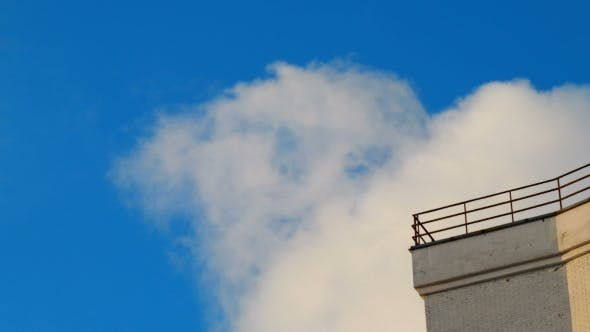 Clip of White Fluffy Clouds Over Blue Sky. and Corner of Building. Beautiful Cloudscape.