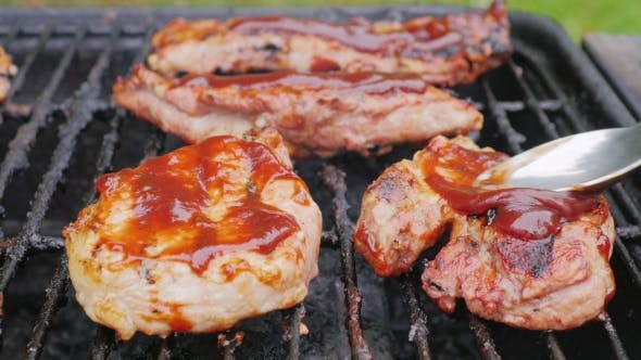 Pieces of Meat on the Grill Smearing Sauce on Top