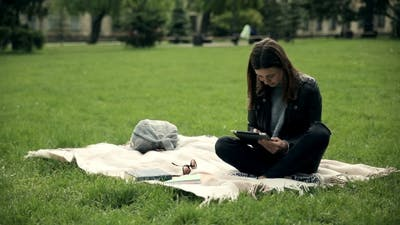 Female Student E-learning Outdoors at Campus.