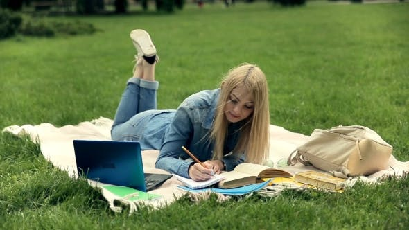 Thumbnail for Female Student Studying on Campus Lawn.