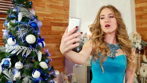 Cover Image for New Year Photo at a Mobile Phone, Girl Doing Selfie, a Festive Party at a Christmas Tree Beautiful