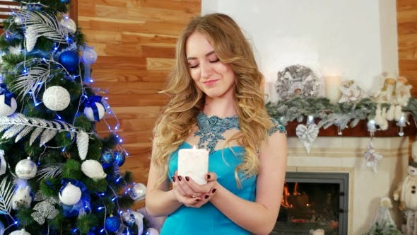 Thumbnail for Girl with a Candle in Hand, Portrait of a Beautiful Female in a Festive Dress Near the Fireplace