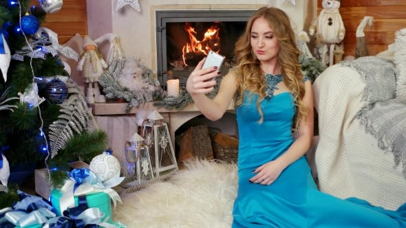 Thumbnail for Girl Doing Selfie Near Burning Fire in the Fireplace, New Year Photo at a Mobile Phone, Beautiful