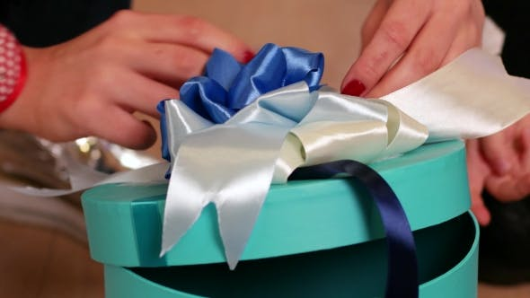 Thumbnail for Gift Wrapping, Girl Knits Bow on a Box with a Gift, a Holiday Surprise for Christmas or a Birthday