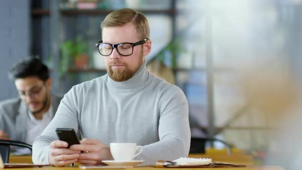 Thumbnail for Young Businessman Texting on Smartphone in Coffeeshop