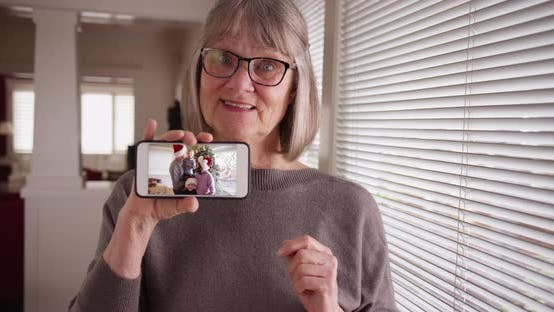 Thumbnail for Caucasian grandmother showing video clip of family during Christmas on phone