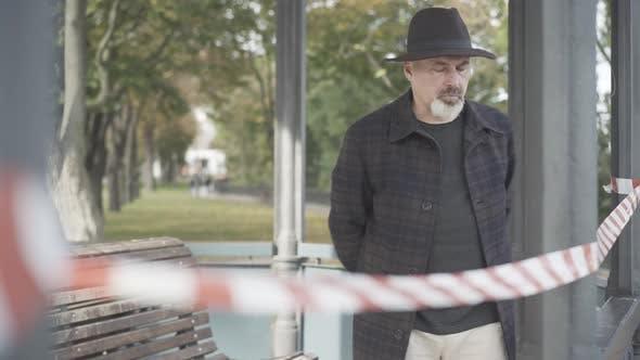 Thumbnail for Mittlerer Schuss eines konzentrierten Ermittlers oder Detektivs, der im Parkpavillon hinter Rot und Weiß geht