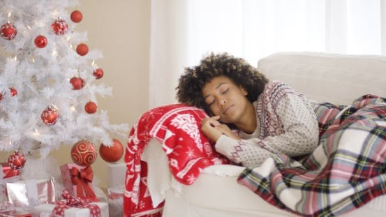 Thumbnail for Woman Sleeping on Couch Beside Christmas Tree