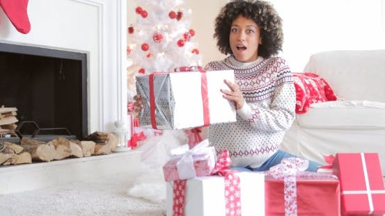 Thumbnail for Surprised Woman Holding a Large Christmas Gift