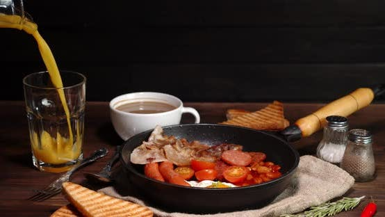 The Plate with the Traditional English Breakfast Rotates. On a Black Background.