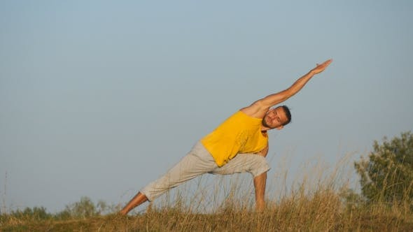 Thumbnail for Caucasian Guy Practicing Yoga Moves and Positions in Nature. Young Sporty Man Standing at Yoga Pose