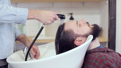 Man Barber Washing Male Hair at Barbershop