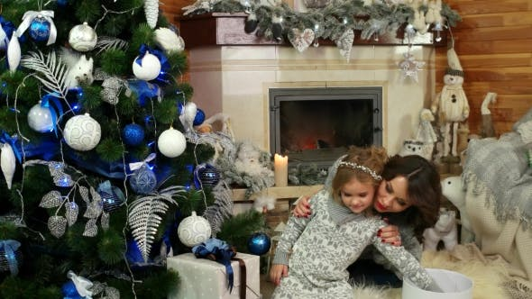 Thumbnail for Mother and Daughter Playing Near the Christmas Tree