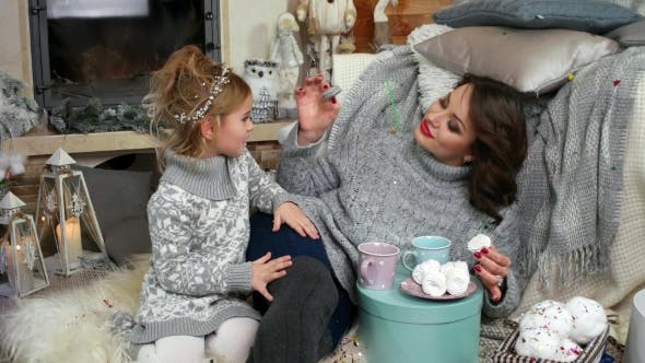 Cover Image for Family By the Fireplace Eating a Dessert with Tea, Mum Feeds the Daughter Macaroon, Mother And