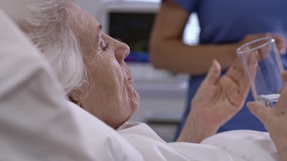 Thumbnail for Nurse Giving Medications to Senior Woman in Hospital