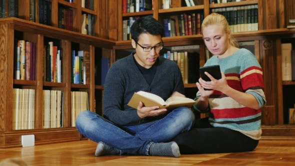 Thumbnail for Friends Sitting on the Floor in the Library. A Man Holding an Open Book, a Woman Used a Tablet