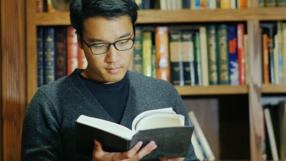 Thumbnail for Good Looking Asian Man in Glasses Reading a Book in the Library. Against the Background of the Stack